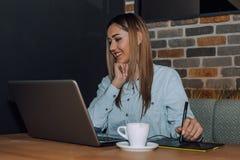 Mujer creativa que trabaja en el ordenador portátil mientras que usa la tableta gráfica en café fotografía de archivo libre de regalías