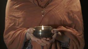 Mujer cristiana que sostiene el cuenco tibetian del canto con la vela metrajes