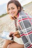 Mujer cubierta con la manta usando la tableta en la playa Imagen de archivo libre de regalías