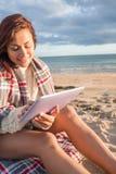 Mujer cubierta con la manta usando la tableta en la playa Imagen de archivo