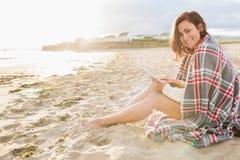 Mujer cubierta con la manta usando la tableta en la playa Fotos de archivo