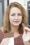 Mujer culpable en dieta que come la barra de chocolate en casa Fotos de archivo