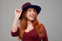 Mujer curiosa del pelirrojo en un sombrero que mira hacia arriba a un poli Fotografía de archivo