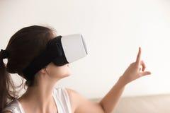 Mujer curiosa en mundo virtual conmovedor de las auriculares de VR por el finger Fotos de archivo libres de regalías