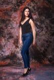 Mujer Curvy hermosa que presenta en camisa negra y vaqueros en fondo multicolor Prueba modelo del tamaño extra grande Fotos de archivo libres de regalías