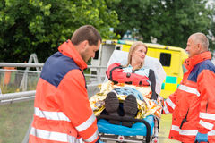 Mujer dañada que habla con emergencia de los paramédicos Imágenes de archivo libres de regalías