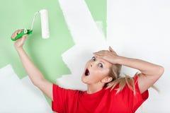 Mujer dada una sacudida eléctrica con el rodillo de pintura a disposición Fotos de archivo libres de regalías