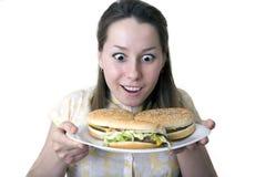 Mujer dada una sacudida eléctrica con las hamburguesas Imagenes de archivo