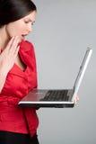Mujer dada una sacudida eléctrica de la computadora portátil Foto de archivo