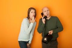 Mujer dada una sacudida eléctrica que escucha la conversación telefónica fotografía de archivo libre de regalías