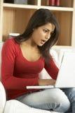 Mujer dada una sacudida eléctrica que usa la computadora portátil Imagen de archivo libre de regalías