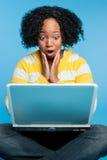 Mujer dada una sacudida eléctrica que usa la computadora portátil Foto de archivo libre de regalías