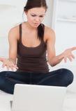 Mujer dark-haired enojada que usa su computadora portátil Imagen de archivo
