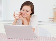 Mujer dark-haired linda que usa su computadora portátil Imagen de archivo
