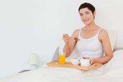 Mujer Dark-haired que desayuna Imagen de archivo libre de regalías