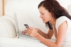 Mujer Dark-haired que hace compras en línea Imagenes de archivo