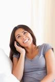 Mujer Dark-haired que telefona mirando el techo Fotos de archivo libres de regalías