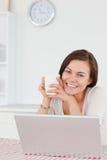 Mujer dark-haired sonriente que usa su computadora portátil Imagenes de archivo