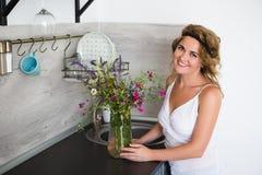 Mujer de 30 años en la cocina con un ramo de flores salvajes Fotos de archivo