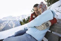 Mujer de abarcamiento del hombre en la ladera Nevado del banco Imágenes de archivo libres de regalías