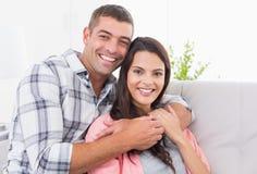 Mujer de abarcamiento del hombre feliz en el sofá Foto de archivo