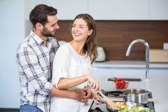 Mujer de abarcamiento del hombre feliz mientras que cocina la comida Foto de archivo libre de regalías