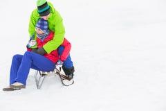Mujer de abarcamiento del hombre joven en el trineo en nieve Imágenes de archivo libres de regalías