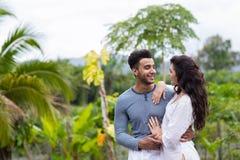 Mujer de abarcamiento del hombre latino feliz, par joven sobre la lluvia tropical verde Forest Landscape Fotos de archivo libres de regalías