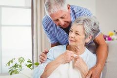 Mujer de abarcamiento del hombre mayor en casa Fotos de archivo libres de regalías