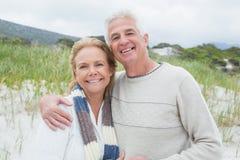 Mujer de abarcamiento feliz del hombre mayor en la playa Foto de archivo libre de regalías