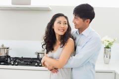 Mujer de abarcamiento sonriente del hombre de detrás en cocina Imagen de archivo