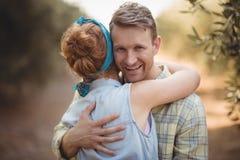Mujer de abarcamiento sonriente del hombre joven en la granja verde oliva Fotos de archivo