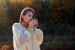 Mujer de admiración hermosa que bebe té caliente de la taza del termo fotografía de archivo