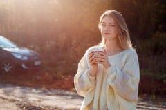 Mujer de admiración hermosa que bebe té caliente de la taza del termo foto de archivo libre de regalías