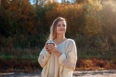 Mujer de admiración hermosa que bebe té caliente de la taza del termo imagen de archivo libre de regalías