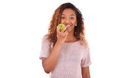 Mujer de Americanyoung del africano que come una manzana verde Fotografía de archivo libre de regalías