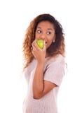 Mujer de Americanyoung del africano que come una manzana verde - peopl negro Imágenes de archivo libres de regalías