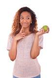 Mujer de Americanyoung del africano que sostiene una manzana verde - peo negro Fotografía de archivo