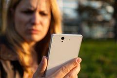 Mujer de Annoyd con smartphone Foto de archivo libre de regalías
