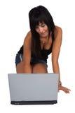 Mujer de arrodillamiento que trabaja en la computadora portátil Imagenes de archivo