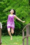 Mujer de Asain que salta en el puente Fotografía de archivo libre de regalías