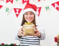 Mujer de Asia en el regalo del partido de Navidad que da la caja del oro al amigo con el SMI Imágenes de archivo libres de regalías