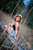 Mujer de Asia en la moda del verano que se sienta en el puente de bambú Fotografía de archivo libre de regalías