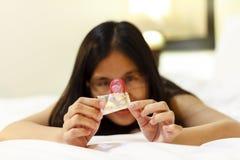 Mujer de Asia que abre un condón en su cama fotografía de archivo