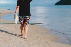 Mujer de Asia que sostiene la sandalia que camina solamente alrededor de la playa de la arena y de la ha Fotos de archivo libres de regalías