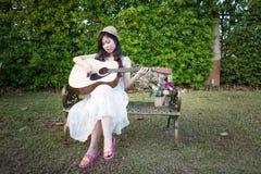 Mujer de Asia que toca la guitarra Imagen de archivo