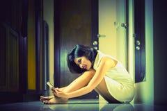 Mujer de Asia que usa el teléfono en sala de estar Foto de archivo