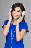 Mujer de Asia que usa su auricular Imagenes de archivo
