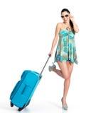 Mujer de ?asual que se coloca con la maleta del viaje Foto de archivo