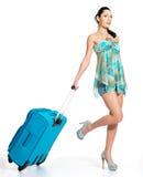 Mujer de ?asual que se coloca con la maleta del viaje Imagen de archivo